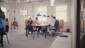 Dockan sköt av teamwork i modern sund arbetsplats Lycklig kvinnlig ledare som hjälper multietniska kollegor med projektet 4K stock video
