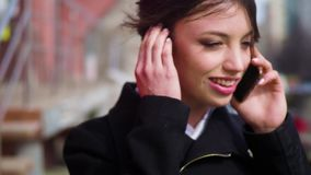 Dockan sköt den attraktiva för affärskvinnan för det blandade loppet talande smartphonen och går i stadsgata arkivfilmer