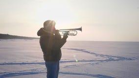Dockan zoomar i skott av bara den caucasian musikern i profilen som aktivt spelar trumpeten i solsken på den djupfrysta naturen lager videofilmer