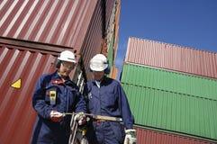 Dockarbeitskräfte und -behälter Stockfoto