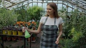 Dockaskott av den attraktiva kvinnaträdgårdsmästaren i förkläde som bevattnar växter och blommor med den trädgårds- sprejaren i v lager videofilmer