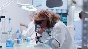Dockaskott av laget som arbetar i modernt laboratorium för högt slut stock video