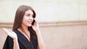 Dockaskottet av den attraktiva för affärskvinnan för det blandade loppet talande smartphonen går i stadsgata lager videofilmer