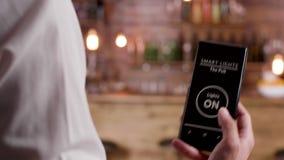 Dockaslut upp skott av bartendern som använder en stämma aktiverad app för att vända PÅ ljusen stock video