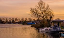 Docked boat at the river den rijn, the Netherlands, beautiful city scenery at sunset with water stock photography