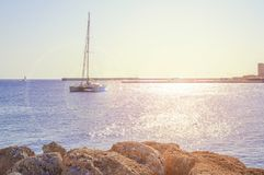 Docked boat at sea near coast with sun flare and clean sky. Background royalty free stock images