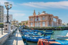 Docked boats with the Margherita Theatre in background, Bari, Apulia, southern Italy. Stock Images
