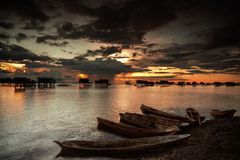 Docked. Docked boats during sunset with floating houses in the background at Bodgaya Island, Sabah, Malaysia royalty free stock image