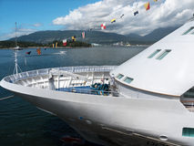 Docked cruise ship with sea and mountains. Cruiseship docked at Canada Place Vancouver Canada preparing to sail to Alaska. View of the bow. Dramatic sky with sea Stock Image
