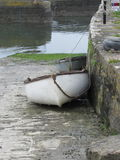 Docked Fishing Boats. Ireland - two row boats tied to post on stone wall Royalty Free Stock Photo