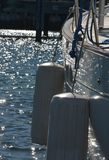Docked. A large sailboat docked and photographed with sun light dancing off its side and the water Stock Image