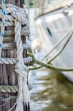 Docked Sailboat and Lines on Pylon. Old worn lines tied to a wooden pylon holding a sailboat to the dock royalty free stock photo