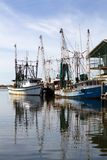 Docked Shrimp Boats. Two old rusty shrimp boats are docked at a pier with reflections in the water stock image