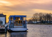 Docked touring boat in the harbor at sunset, beautiful colorful sky with city scenery stock images
