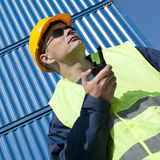 Docker. Observing docker in front of a stack of blue containers on a bright sunny day wearing sunglasses Stock Image