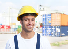 Docker laughing at camera on a seaport. With containers for oversea in the background Stock Image