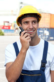 Docker on a seaport at work. Young docker on a seaport at work speaking to a radio device Royalty Free Stock Image