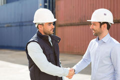 Docker and supervisor handshaking in front of containers Royalty Free Stock Photos