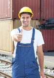 Docker at work showing thumb up. At the seaport with containers for oversea in the background Royalty Free Stock Images