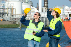Dockers. Two dock workers at inspection, looking up Stock Photos