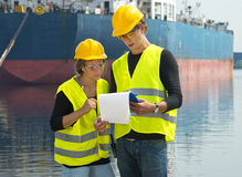 Dockers checking freight papers. Two dockers checking the freight papers of a cargo vessel moored off in the background in a harbor Royalty Free Stock Photography