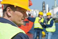 Dockers portrait. Portrait of a docker in front of a harbor scene with two of his coworkers out of focus in the background Royalty Free Stock Image