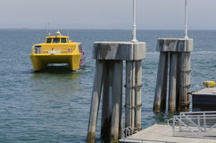 Docking Boat. A catamaran-style passenger boat approaches a pier Stock Images