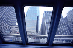 Docking in lower manhattan. View of lower manhatten  from commuter ferry boat windows. The financial district skyscrapers are seen through the windows..Symbols Stock Photography