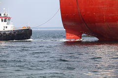 Docking Maneuver. A tugboat takes a cargo vessel on the leash royalty free stock image
