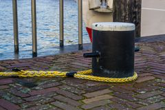 Docking pole with a rope to secure the boat, equipment at the harbor, water transportation background. Docking pole with a rope to secure the boat, equipment at stock photo