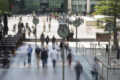 Docklands clocks. Early morning workers rush past the clocks in london's docklands financial district stock image