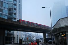 Docklands Light Railway Train over Road. A London Docklands Light Railway (DLR) train passes over a road on a dull foggy morning in Poplar, East London Stock Photography