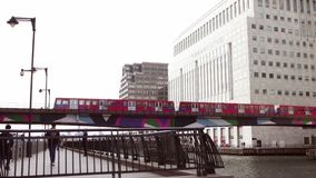 Docklands Light railway train passes buildings in Canary Wharf stock video footage