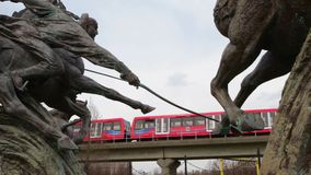 Docklands Light Railway train passes statues near Royal Albert Station stock footage