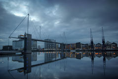 Docklands Reflection. An almost perfectly smooth surface on the Royal Victoria Dock basin, just before dawn. The suspension bridge stands out against the rich Royalty Free Stock Photos