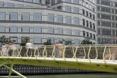 Docklands workers. Long exposured shots capturing blurred business people walking across bridge in docklands, london Stock Photo