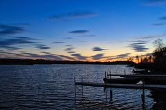 Sunset over large lake and docks jutting into water located in Hayward, Wisconsin. Docks jut out into large lake in Hayward, Wisconsin, with ripples from the Royalty Free Stock Photo