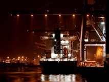 Docks At Night. A ship at the docks being loaded with containers at night Stock Photos