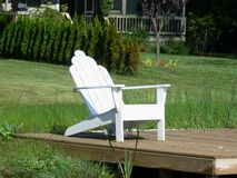 Dockside Adirondack Chair. Peaceful dockside adirondack chairs on the edge of a lake in Michigan Royalty Free Stock Photos