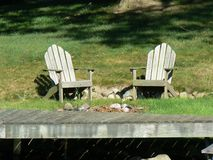 Dockside Adirondack Chairs. Peaceful dockside adirondack chairs on the edge of a lake in Michigan Royalty Free Stock Images