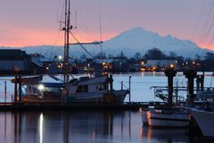 Dockside Morning Steveston. In the early morning, commercial fishboats reflect in the calm water of Steveston Harbor, British Columbia near Vancouver. Steveston Royalty Free Stock Photo