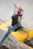 Dockworker Ties Mooring Lines to a Bollard Royalty Free Stock Photo