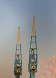 Dockyard Cranes. Two dockyard cranes against a blue sky Royalty Free Stock Photography