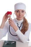 Docotr femenino que examina el corazón rojo Imágenes de archivo libres de regalías