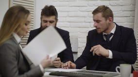 Счастливая молодая команда бизнесмена и коммерсантки работая вместе с бумажными docs на столе обсуждая информацию в офисе видеоматериал