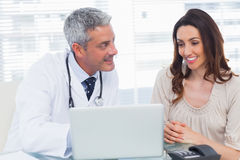 Docter showing something on laptop to his patient. In medical office royalty free stock photo
