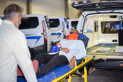 Docter taking patient out ambulance on stretcher. Docter taking patient out of ambulance on a stretcher royalty free stock images