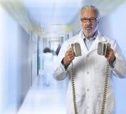 Docteur à l'aide d'un défibrillateur images libres de droits