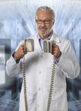 Docteur à l'aide d'un défibrillateur images stock