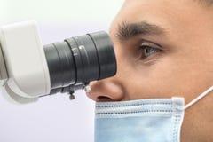 Docteur à l'aide d'un microscope dentaire images stock